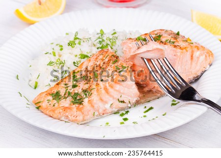 Steamed salmon with fresh herbs and lemon. Rice as a garnish - stock photo