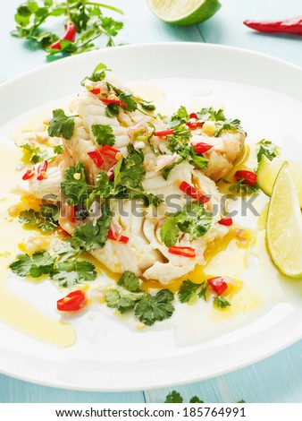 Steamed sea bass fillet with chili pepper and cilantro in olive and linseed oil. Shallow dof.