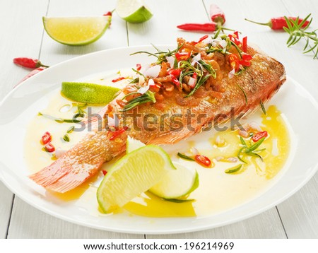 Steamed sea bass with chili pepper, rosemary, bacon and shallot onion in olive and linseed oil. Shallow dof. - stock photo