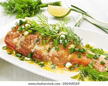 Steamed sea bass with fennel and leek in olive and linseed oil. Shallow dof. - stock photo