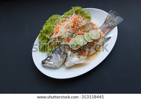 Steamed snapper with lemon on black background.  - stock photo