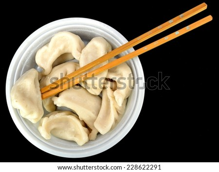 Steamed vegetable dumplings with chop sticks on a black background. - stock photo