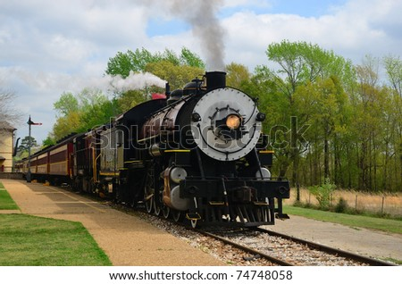 Steamer engine and passenger cars arrive at the depot. - stock photo