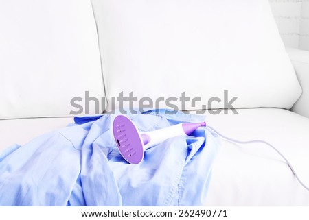 Steamer for clothes and shirt in room - stock photo