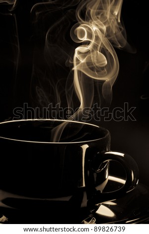 Steaming black coffee cup on black background - stock photo