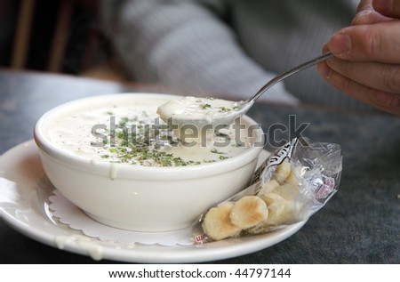 Steaming bowl of white New England clam chowder with crackers on the side - stock photo