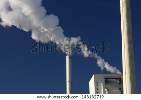 Steaming chimneys of power plant - stock photo
