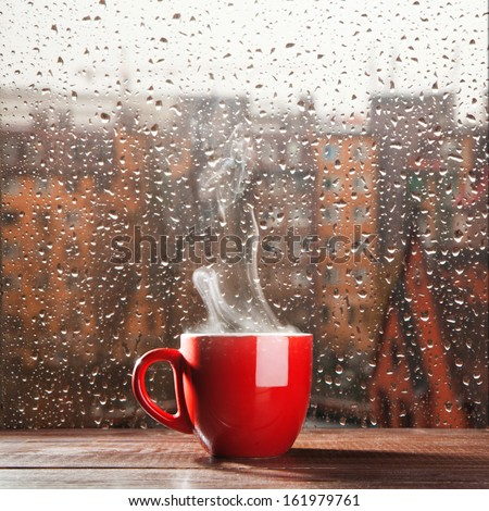 Steaming coffee cup on a rainy day window background - stock photo