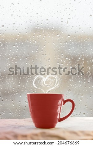 Steaming coffee cup on a rainy day window background with heart shape   - stock photo