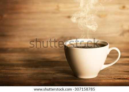 Steaming coffee in white cup in soft focus setting with dramatic ambient light, over dark wooden background. - stock photo