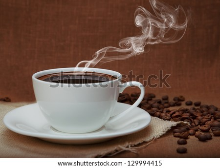 steaming coffee on flax background - stock photo