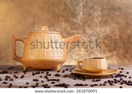 Steaming coffee on old wooden table - vintage setup on golden background - stock photo