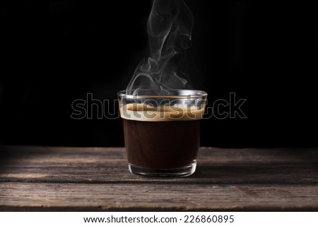 Steaming coffee over wooden surface and black background - stock photo