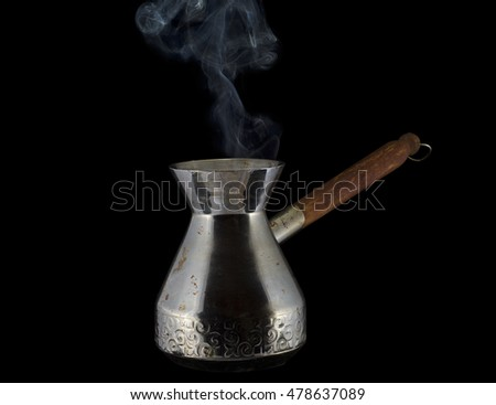 Steaming coffee pot, isolated on black background. Clipping path included