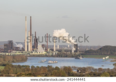 Steaming Coking Plant at the river Rhine near Duisburg, Germany with some ships on the river.