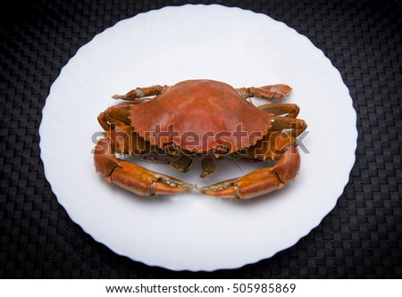 Steaming crab in white dish.