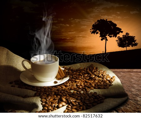 Steaming cup of coffee, cinnamon sticks and a few coffee beans. still life - stock photo