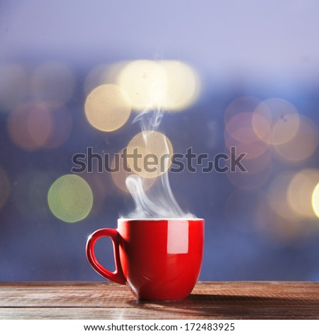 Steaming cup of coffee over a cityscape background - stock photo