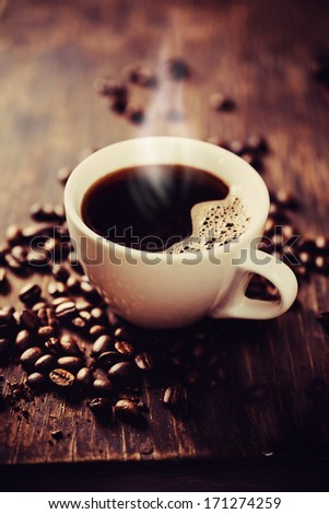 Steaming cup of freshly brewed coffee. Shallow depth of field - stock photo