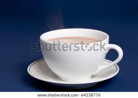 Steaming cup of hot cocoa on blue background - stock photo
