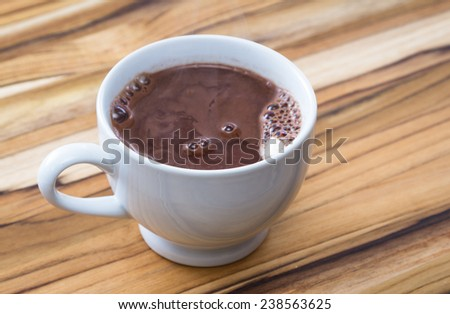 steaming cup of hot cocoa over a tropical teak wood background - stock photo
