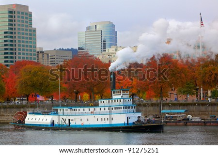Steaming ferry paddle boat with softer background of trees and the city of Portland - stock photo