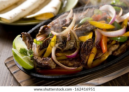 Steaming hot steak fajita in a cast iron skillet. - stock photo