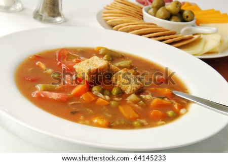 Steaming hot vegetable soup with crackers and cheese for appetizers