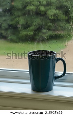 Steaming mug of coffee on a window sill with raindrops on window - stock photo