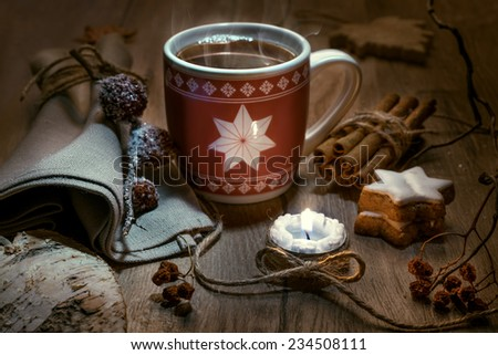 Steaming mug of tea on wooden table with winter decorations - stock photo