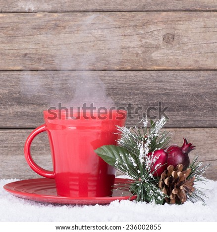 Steaming red coffee cup with a Christmas ornament on a wooden background - stock photo