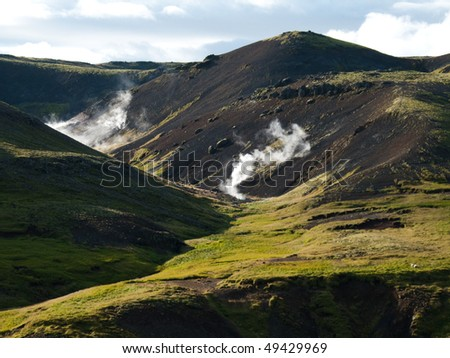 steaming river, black lava mountains and sheep in the valley Reykjadalur in Iceland