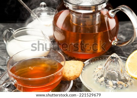 Steaming tea in tea service of glass