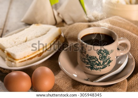 Steaming traditional oriental Chinese kopitiam style dark coffee in vintage mug and saucer with coffee beans. Fractal on the cup is generic print. Soft focus with dramatic light on wooden background. - stock photo