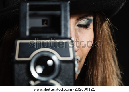 Steampunk. Closeup retro woman with old vintage camera studio shot grunge dark background