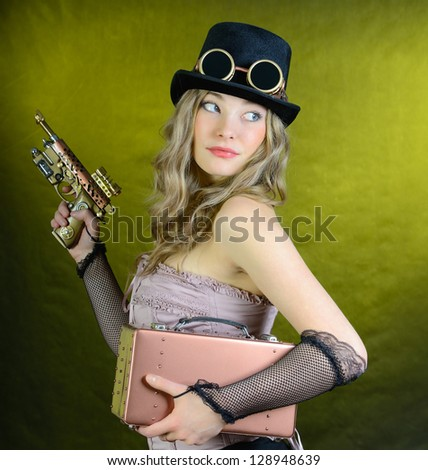 Steampunk girl with pistol and small suitcase to look back - stock photo