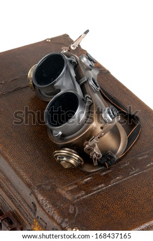 Steampunk goggles over a suitcase isolated in white