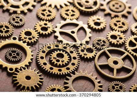 steampunk mechanical cogs gears wheels on wooden background - stock photo