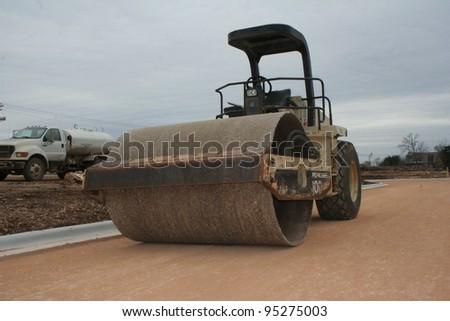 Steamroller on new city street - stock photo