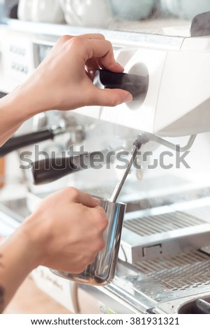 Steamy shot. Barista steaming milk at the local coffee shop closeup shot