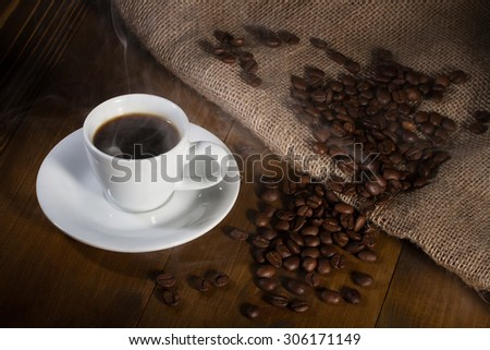 Steamy white coffee cup and beans on wooden table with sacking - stock photo