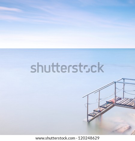 Steel and wooden old ladder pier in a cold atmosphere. Long exposure photography. - stock photo