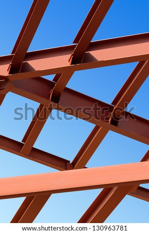 Steel beams against the blue sky. Fragment construction site. - stock photo