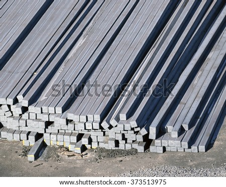 steel billets stacked to loading on a ship in port - stock photo