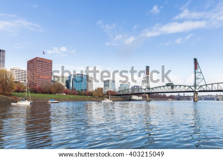 steel bridge over tranquil water with cityscape and skyline of portland