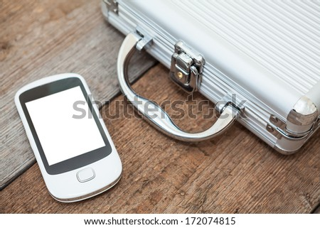 Steel briefcase with mobile phone laying on the wooden floor - stock photo