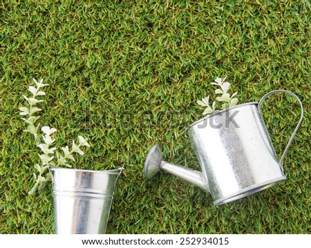 steel bucket, watering can and plant on green grass turf - stock photo