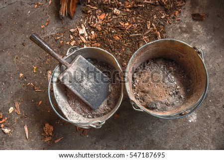 Steel buckets filled with ash from a domestic household fireplace on the concrete floor of a barn with wood chippings close by