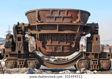 Steel buckets to transport the molten metal, mounted on railway platforms. - stock photo