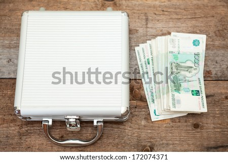 Steel case with Russian rubles on wooden floor - stock photo